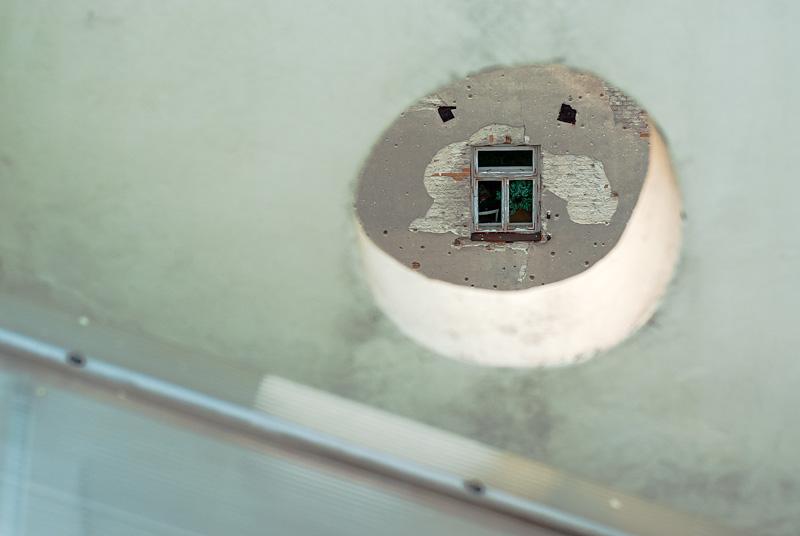 Dziura, kamienica i okno.